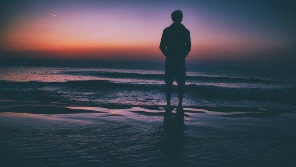 Man die op een strand staat, want een van de kenmerken van emotionele volwassenheid is nadenken over je toekomst