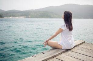 Vrouw die mediteert aan het water, maar wat zegt de wetenschap over meditatie?