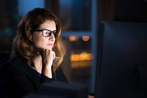 Vrouw die 's nachts op de computer werkt