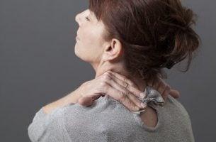 Vrouw die last heeft van nekpijn, daarom moet je goed voor je nek zorgen