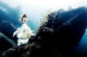 Meisje dat onder water staat en omhoog kijkt, want je dieptepunt bereiken maakt dat je alleen nog maar omhoog kunt