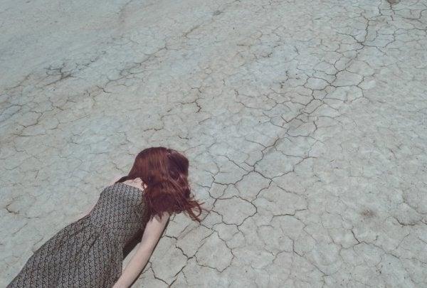 Meisje dat met haar haar over haar gezicht op droog landschap ligt, omdat ze last heeft van paniekaanvallen