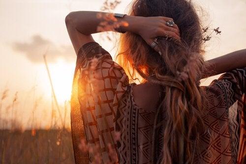 Vrouw die naar een zonsondergang kijkt in een open veld, want ze wil spontaner zijn