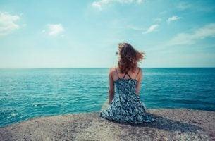 Vrouw die over de zee uitkijkt