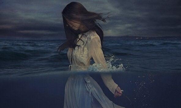 Vrouw die met haar kleding aan de zee in loopt, want woede is giftig