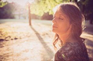 Een van de vrouwen met borstkanker die geniet van de zon op haar gezicht