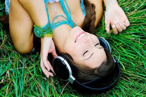Vrouw die in het gras muziek ligt te luisteren