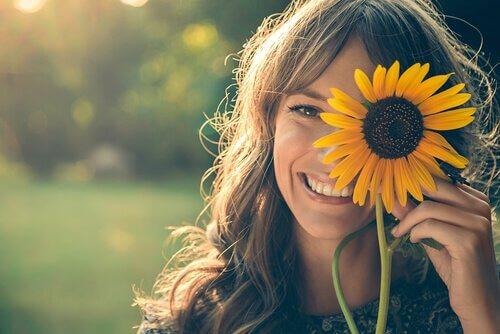 Meisje dat een zonnebloem voor haar oog houdt en glimlacht, want je lach kan de wereld veranderen