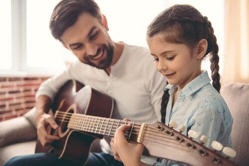 Vader leert kind gitaar spelen