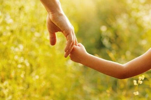 Vader en kind houden elkaars hand vast