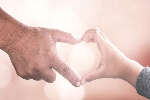 Hand van een oudere man die samen met de hand van een kind een hartje vormt