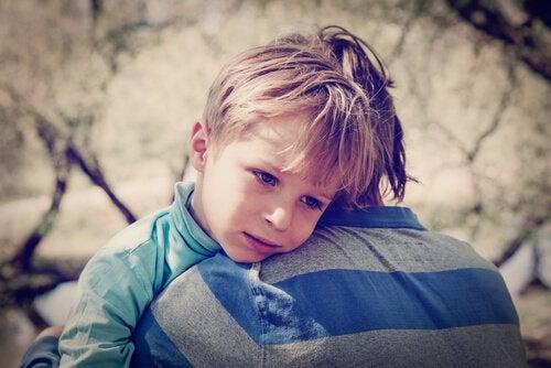 Verdrietig jongetje dat geknuffeld wordt door een volwassene