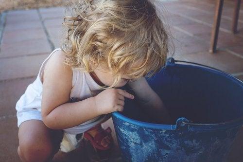 Klein kindje dat in een emmer graait