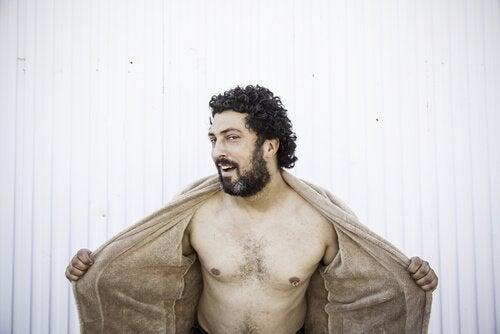 Een man opent zijn jas en toont zijn borstkas