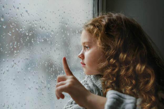 Meisje dat droevig uit het raam kijkt
