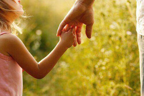Een meisje houdt de hand van haar vader vast