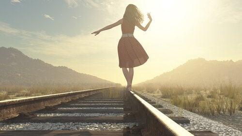 Vrouw die over een treinspoor loopt