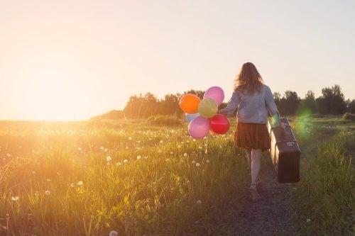 Vrouw met koffer en ballonnen in een veld