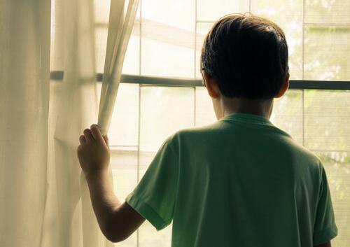 Kind kijkt uit het raam