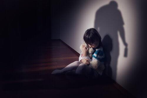 Kind met een teddybeer in de schaduw van zijn vader