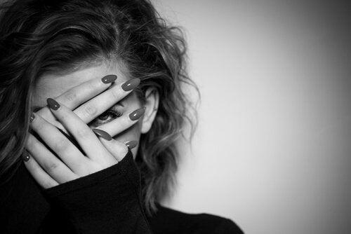 Vrouw die door haar vingers kijkt