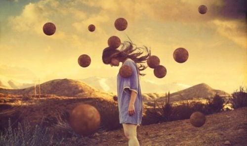 Meisje omringd door zwevende ballen