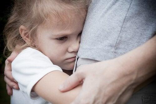 Verdrietig meisje houdt moeder stevig vast