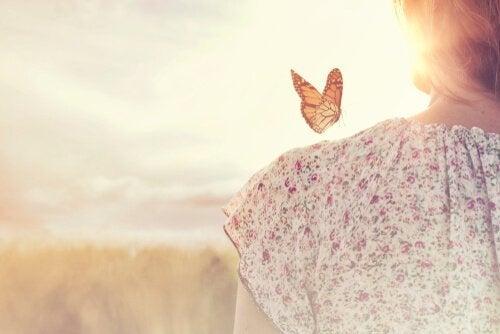 Vrouw met vlinder op haar schouder