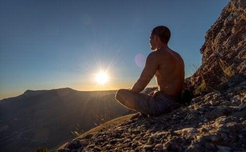 Man mediteert op een rots