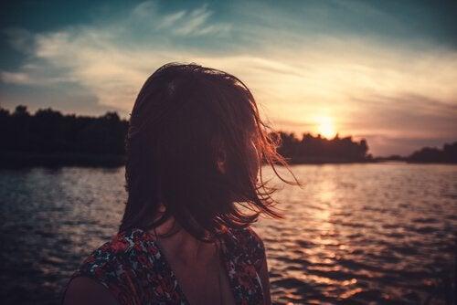 Vrouw die over het water naar de zon kijkt