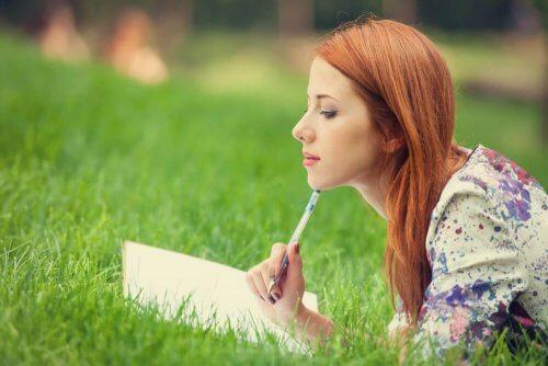 Vrouw leest boek in het gras