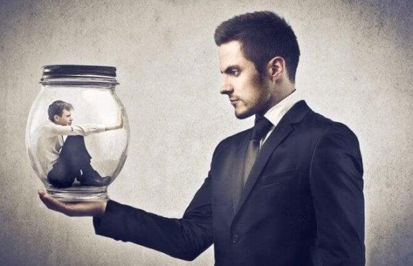 Man houdt glazen pot vast met daarin een andere man