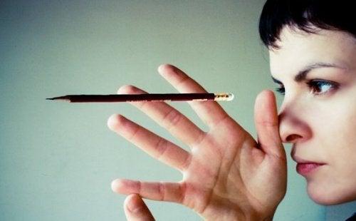 Vrouw die langs haar potlood kijkt