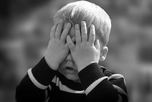 Kind met handen voor het gezicht