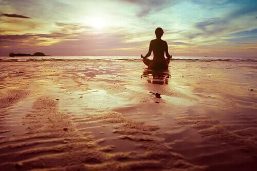 Persoon mediteert op het strand