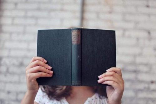 Vrouw bedekt haar gezicht met een boek