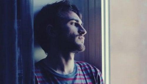 Droevige jongen kijkt uit raam