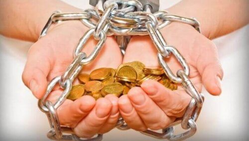 Geketende handen die geld vasthouden