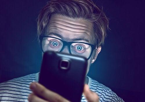 Men kijkt op het scherm van een mobiele telefoon