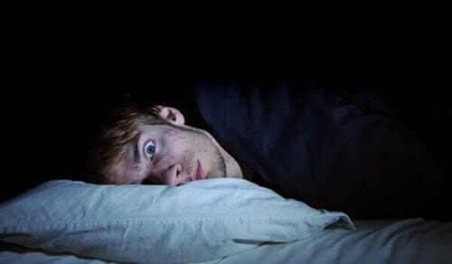 Man ligt met open ogen in bed