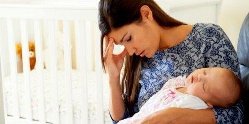 Uitgeputte moeder met baby in haar armen