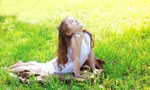 Meisje doet yoga in het gras