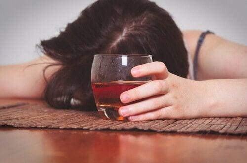 Dronken vrouw met glas alcohol in haar hand