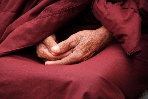 Handen van een mediterende oude man