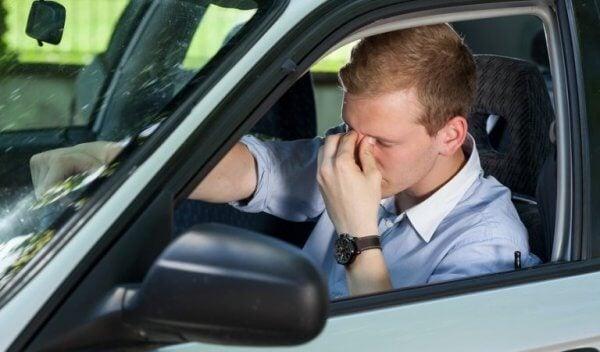 Man wrijft in zijn ogen achter het stuur van zijn auto