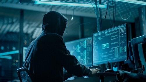 Man met capuchon achter computerschermen