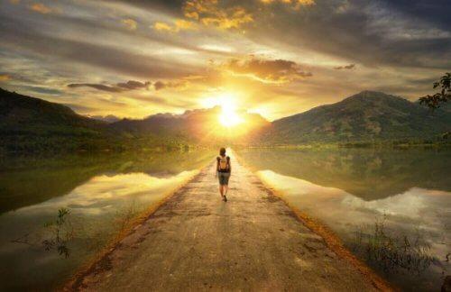 Man loopt richting zonsondergang