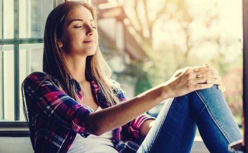 Vrouw zit tevreden in het zonlicht