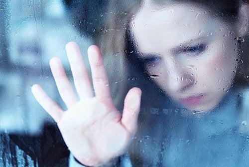 Meisje kijkt droevig uit raam