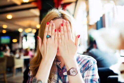 Vrouw verbergt zich achter handen uit schaamte